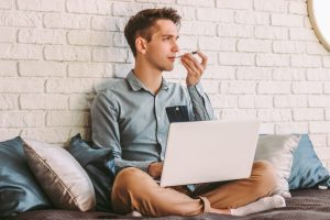 Man working from home taking his temperature